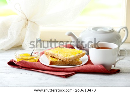Toasts with honey on plate and cup of tea on light background - stock photo