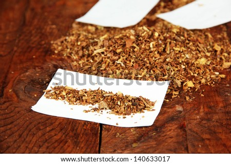 Tobacco and rolling paper, on wooden background - stock photo