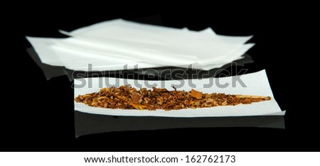 Tobacco and rolling papers, isolated on black - stock photo
