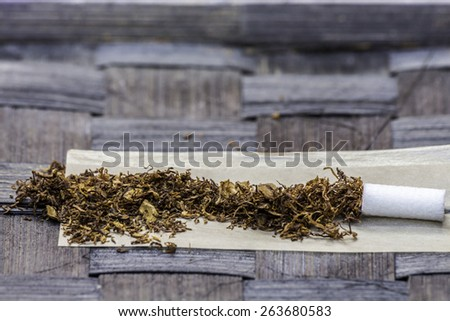 Tobacco in Rolling Paper with a Slim Filter - stock photo