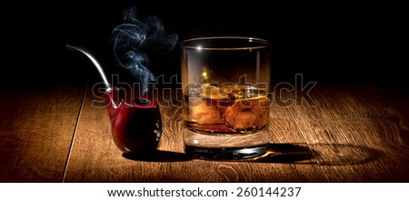 Tobacco pipe and glass of scotch on wooden table - stock photo