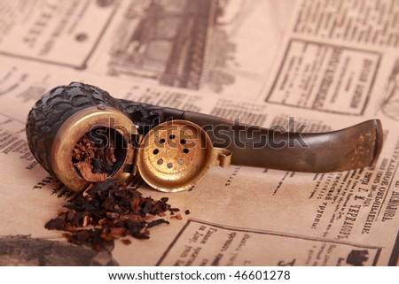 Tobacco pipe on old paper - stock photo