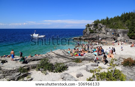 TOBERMORY, ONTARIO/CANADA - JULY 1: Tourists gather at Indian Head Cove on July 1, 2012 in Tobermory. The cove is located in Bruce Peninsula National Park on the shores of Georgian Bay. - stock photo