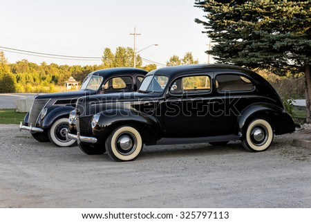 TOBERMORY, ONTARIO - SEPTEMBER 26: Two black vintage Ford automobiles with equipped with white wall tires parked near the road, photographed in Tobermory on Sept 26, 2015 .   - stock photo