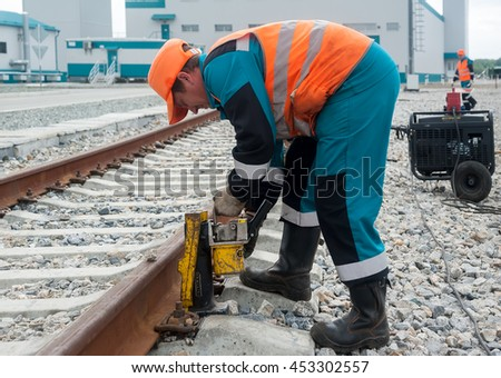 Tobolsk, Russia - July 15. 2016: Sibur company. The worker establishes jack for lifting rails for the purpose of repair of a railroad body - stock photo