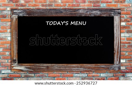 Today's menu on vintage chalk board over brick wall background - stock photo