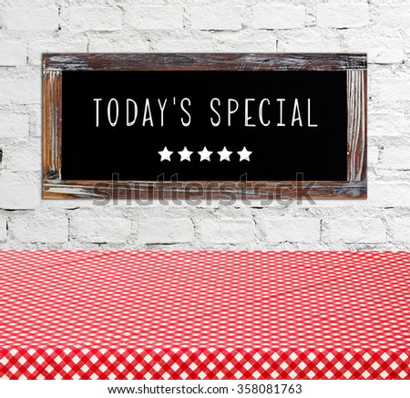 Today's special on vintage chalk board over empty table covered with red check tablecloth, food and drinks background, food display montage - stock photo