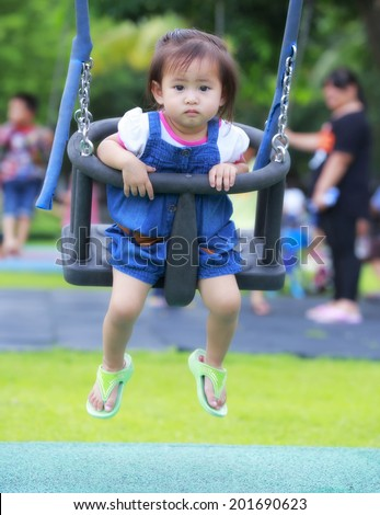 Toddler asia girl with  wearing a blue dress having fun on a swing enjoying on a playground in a park  - stock photo