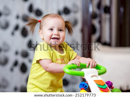 Toddler baby standing with support at home - stock photo