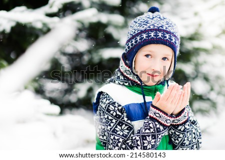 Toddler boy having fun outdoors on beautiful winter day - stock photo