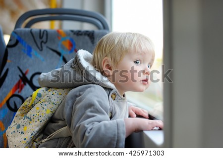 Toddler boy looking out train or tram window  - stock photo