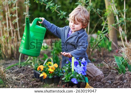 Toddler boy of 2 gardening and planting vegetable plants and flowers in garden, outdoors - stock photo
