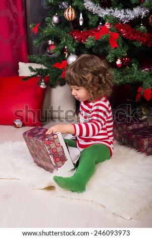 Toddler boy opening Christmas gift under tree - stock photo