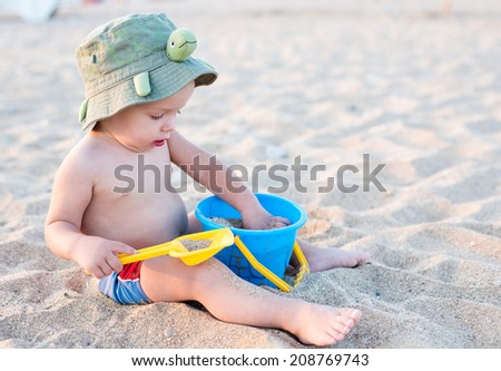 Toddler boy playing on the beach in summer - stock photo