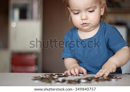 Toddler boy playing with a lot of scattered coins, indoor financial concept - stock photo