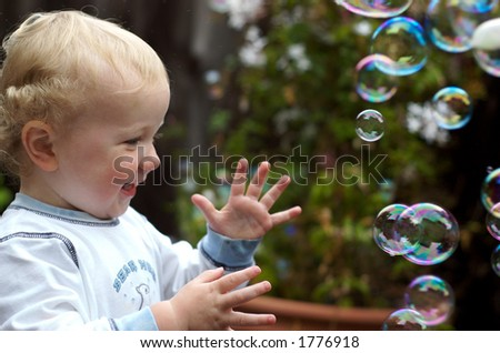 toddler boy playing with bubbles one - stock photo