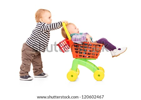 Toddler boy pushing his twin sister in a toy cart isolated on white background - stock photo