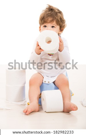 Toddler boy sitting on potty holding rolls paper and looking up  - stock photo