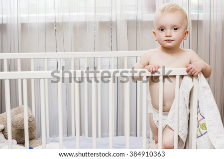 toddler boy standing in his crib holding a blanket serious - stock photo