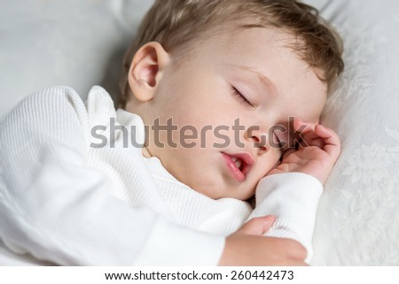 Toddler boy sweetly asleep on a pillowon a white background - stock photo