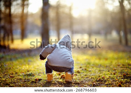 Toddler boy walking outdoors at the warm spring day  - stock photo