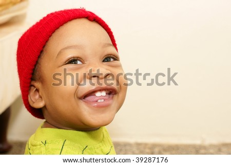 toddler boy with smiling with red toque - stock photo