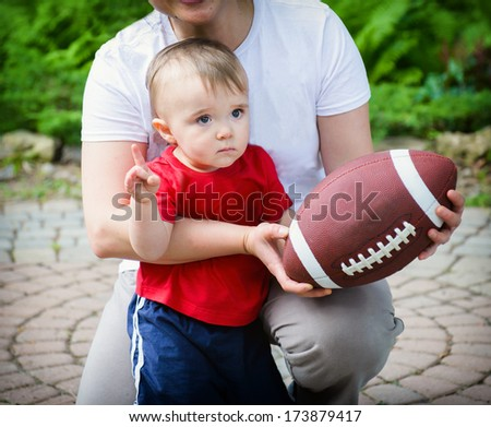 """Toddler child declares """"We're Number One!"""" in support of his team, but his heart is not at all in it.  - stock photo"""