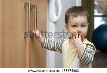 Toddler child in kitchen, children safety at home concept.  - stock photo