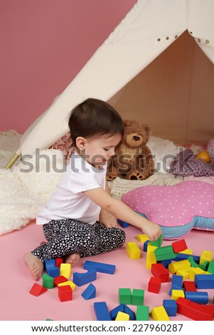 Toddler child, kid, engaged in pretend play with building blocks, toys, and teepee tent - stock photo