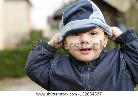 Toddler child playing outside trying to put on his hat. - stock photo