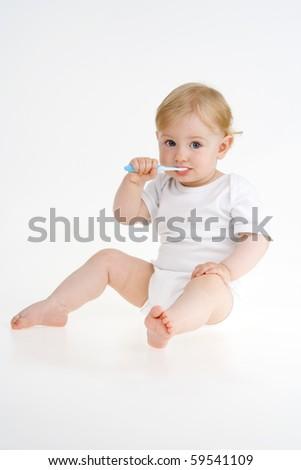 Toddler clears teeth on white background. - stock photo