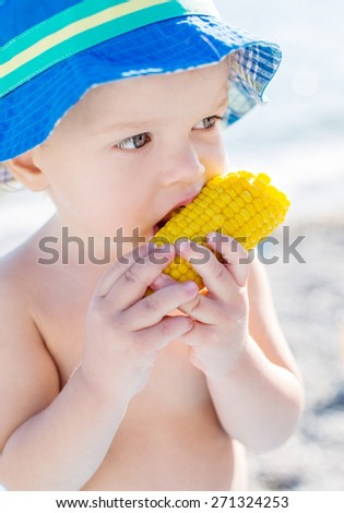 Toddler cute boy eating boiled corn on the sea - stock photo