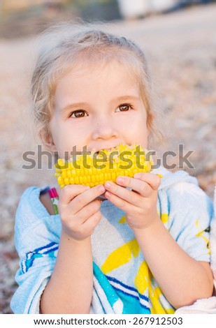 Toddler cute girl eating boiled corn on the sea - stock photo