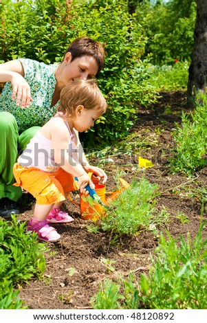 Toddler daughter helping mother in the garden - stock photo