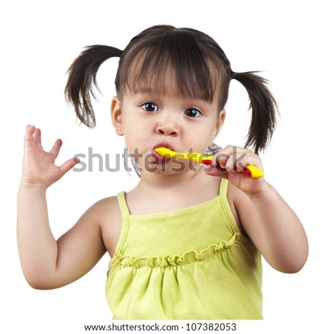 Toddler doing dancing moves while brushing her teeth - stock photo