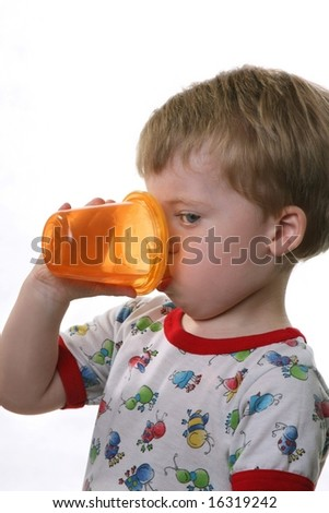 Toddler drinking from orange cup - stock photo