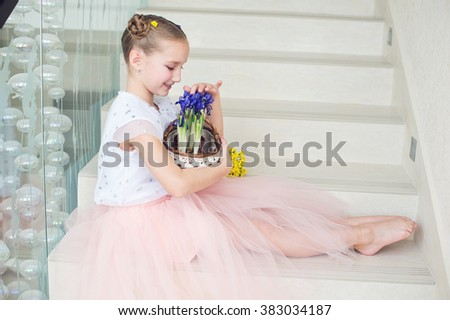 Toddler funny ballerina girl at home ready to celebrate spring and Easter with flowers basket - stock photo