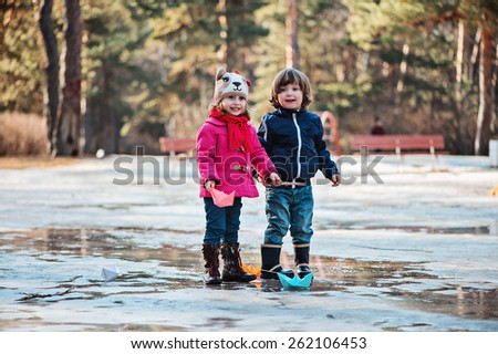 toddler girl and boy having fun on the early spring walk with paper boats in hands - stock photo