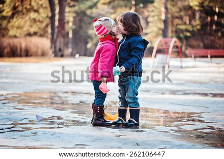 toddler girl and boy kisses on the early spring walk with paper boats in hands - stock photo