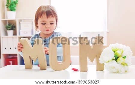 Toddler girl celebrating Mothers Day with big MOM letters - stock photo