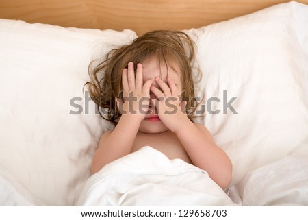 Toddler Girl closing her eyes in the bed, perhaps she is seeing bad dreams. - stock photo