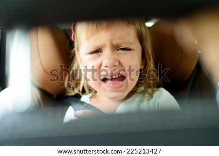 toddler girl crying in car - stock photo