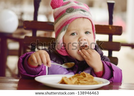 toddler girl eating in outdoor cafe - stock photo