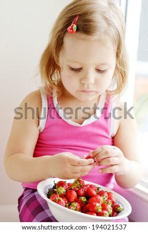 toddler girl eating strawberry near the window - stock photo
