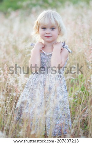 Toddler girl in a field - stock photo