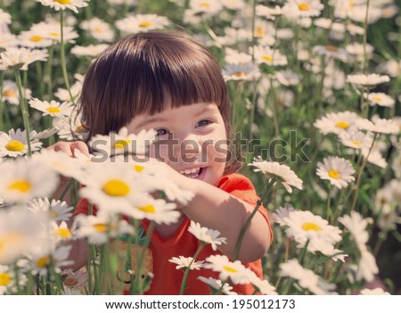 toddler girl in the daisy field - stock photo