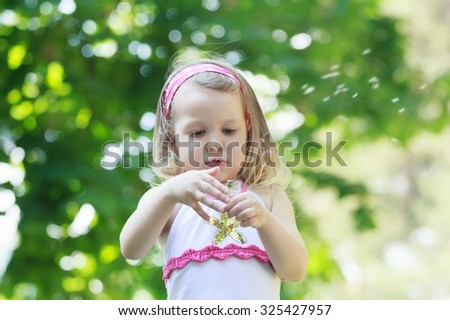 Toddler girl is blowing on white Taraxacum officinale or common dandelion seeds in her arm - stock photo