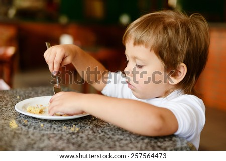 toddler girl is eating with fork in cafe - stock photo