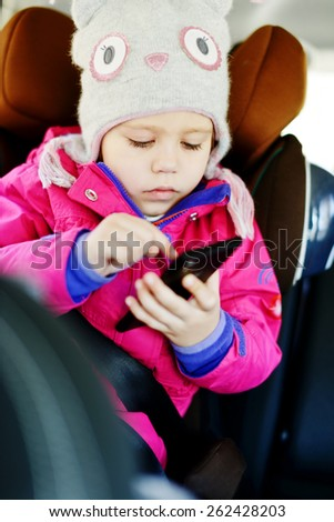 toddler girl is playing smartphone in the car - stock photo