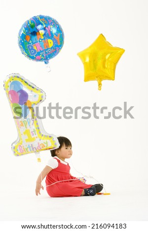 Toddler girl (9-12 months) with baloons, side view - stock photo